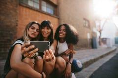 Trois amis féminins de sourire faisant le selfie Photos stock