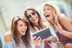 Trois amis féminins de sourire heureux partageant une tablette Photos libres de droits