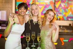 Trois amis féminins de sourire se tenant avec le bras autour dans la barre Images stock