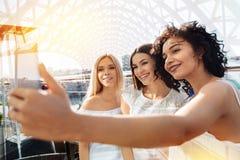 Trois amis féminins enthousiastes enregistrant ce jour Image stock