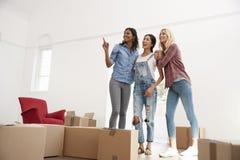 Trois amis féminins entrant dans la nouvelle maison ensemble Photos libres de droits