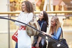 Trois amis féminins faisant des emplettes dans le mail ensemble Images stock