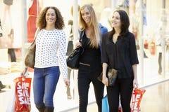 Trois amis féminins faisant des emplettes dans le mail ensemble Image stock