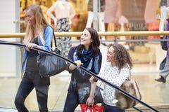 Trois amis féminins faisant des emplettes dans le mail ensemble Image libre de droits