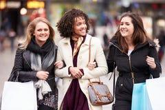 Trois amis féminins faisant des emplettes dehors ensemble Image libre de droits
