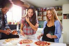 Trois amis féminins faisant la pizza dans la cuisine ensemble Photographie stock libre de droits
