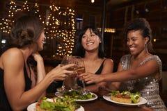 Trois amis féminins font un pain grillé au-dessus de dîner au restaurant Image stock