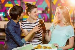 Trois amis féminins grillant la bouteille de bière Image stock
