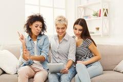 Trois amis féminins heureux à l'aide du comprimé Image stock