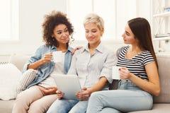 Trois amis féminins heureux à l'aide du comprimé et buvant du café Image libre de droits