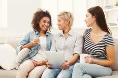 Trois amis féminins heureux à l'aide du comprimé et buvant du café Photo libre de droits