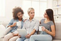 Trois amis féminins heureux à l'aide du comprimé et buvant du café Photos libres de droits