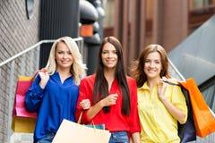 Trois amis féminins heureux attirants marchant au centre de la ville avec des paniers Photo libre de droits