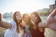 Trois amis féminins heureux prenant le selfie sur la plage Photographie stock libre de droits