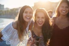 Trois amis féminins heureux se tenant ensemble sur la plage Photographie stock libre de droits