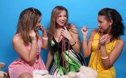 Trois amis féminins mordant des programmes Photographie stock libre de droits