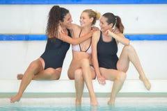Trois amis féminins par la piscine latérale Image stock