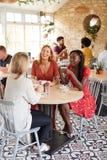 Trois amis féminins parlant au-dessus du brunch à un café, verticale photos libres de droits