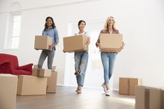 Trois amis féminins portant des boîtes dans la nouvelle maison le jour mobile Photo libre de droits