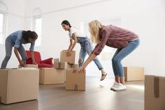 Trois amis féminins portant des boîtes dans la nouvelle maison le jour mobile Photographie stock