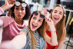 Trois amis féminins prenant le selfie faisant des visages soulevant des lunettes de soleil en habillement et débouché d'accessoir Photos stock
