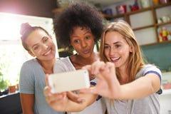 Trois amis féminins prenant Selfie tout en faisant le petit déjeuner Images libres de droits