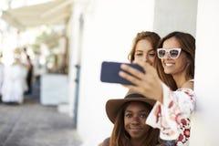Trois amis féminins prenant un selfie dans la rue, Ibiza Photos stock