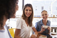 Trois amis féminins se réunissant dans le café Photographie stock