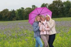 Trois amis féminins sous le parapluie extérieur Images libres de droits