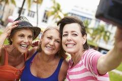 Trois amis féminins supérieurs prenant Selfie en parc Photographie stock