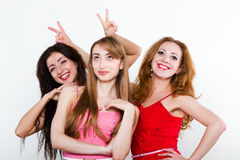 Trois amis féminins sur le fond blanc Image stock
