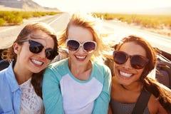 Trois amis féminins sur le voyage par la route derrière la voiture convertible Image stock