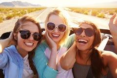 Trois amis féminins sur le voyage par la route derrière la voiture convertible Photographie stock