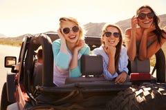 Trois amis féminins sur le voyage par la route derrière la voiture convertible Photographie stock libre de droits