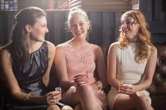 Trois amis féminins tenant le verre à liqueur de tequila dans la barre Image stock