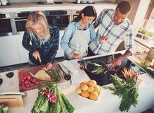 Trois amis faisant cuire à la cuisine Photo stock