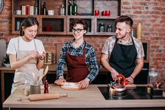 Trois amis faisant cuire des repas ensemble Images libres de droits