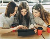 Trois amis faisant des emplettes au magasin en ligne Photographie stock