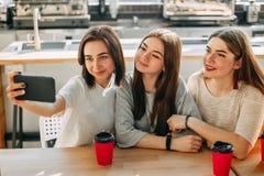 Trois amis faisant le selfie boire du café au café Photo stock