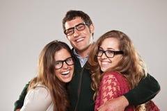 Trois amis futés d'étudiant regardant avec des lunettes Photos stock