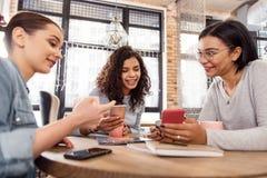 Trois amis gais à l'aide des smartphones Image stock