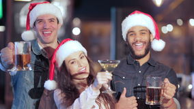 Trois amis gais dans le chapeau de Santa avec des verres banque de vidéos
