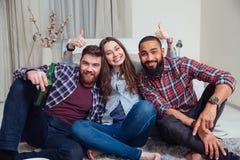 Trois amis gais reposant et montrant des pouces à la maison Photos stock