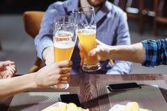 Trois amis grillant avec des verres de bière blonde au bar Images libres de droits