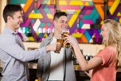 Trois amis grillant des verres de bière Photographie stock libre de droits