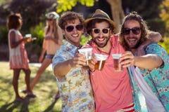 Trois amis grillant des verres de bière Image libre de droits