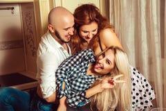 Trois amis heureux ayant l'amusement à la partie de maison Image stock