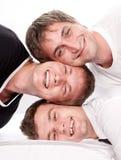 Trois amis heureux ayant l'amusement sur un blanc Photo stock