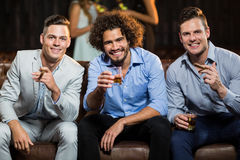 Trois amis heureux ayant le cigare et le whiskey dans la barre Photos libres de droits