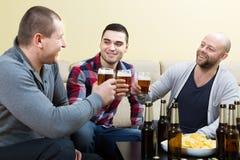 Trois amis heureux buvant de la bière Image libre de droits